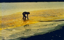 A clean-up worker in the process of skimming oil as part of the clean-upprocess after the World Prodigy oil-spill.