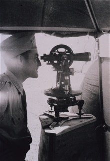 Lieutenant Raymond M. Stone observing angles during triangulation survey at C&GS; Station CASS, a 1st Order station.  Using a Parkhurst 9 theodolite.In the vicinity of Willcox, Arizona, April 1946.