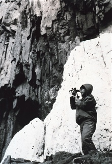 Lt. (j.g.) Ray Stone off the C&GS; Ship E. LESTER JONES observing a verticalsextant angle at Station CAVE on Cape Korovin, Atka Island.  May 17, 1943.