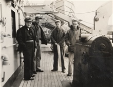 Lieutenant Miller J. Tonkel holding boat sheet with Chief Engineer on left andtwo unidentified junior officers on board USC&GS; Ship PATHFINDER.