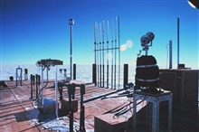 Instruments mounted on the roof of the Clean Air Facility.  Air sampling stacksin the center and pyrheliometer on the right.